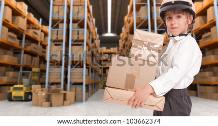 Child wearing a motorbike helmet carrying parcels in a transportation warehouse - stock photo