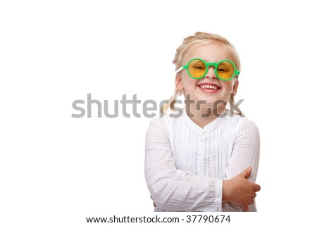 Child wears green glasses and smiles happy into camera. Isolated on white background. - stock photo