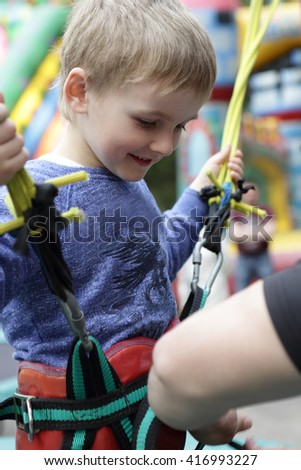 Child wears outfit for jumping on a trampoline with a rubber band