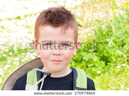 Child with a backpack and hat outdoors - stock photo