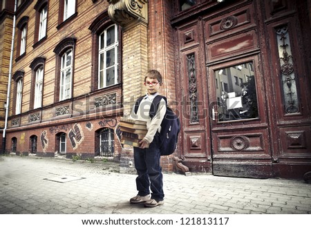 Child with a backpack holding some books near a school