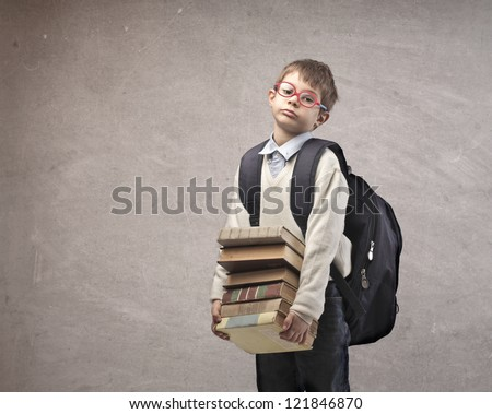 Child with a backpack holding some school books - stock photo