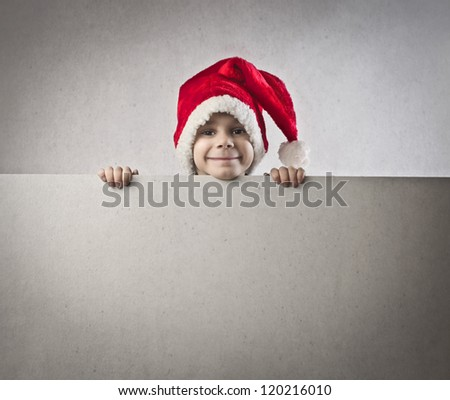 Child with a christmas hat appearing over a blank billboard - stock photo