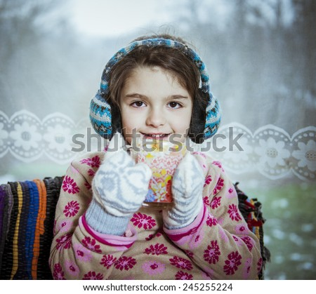Child with a cup of tea .winter time. - stock photo