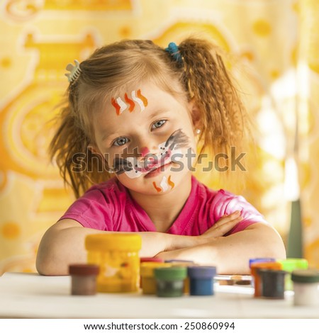 Child with a face painted with colorful paints (squares series) - stock photo