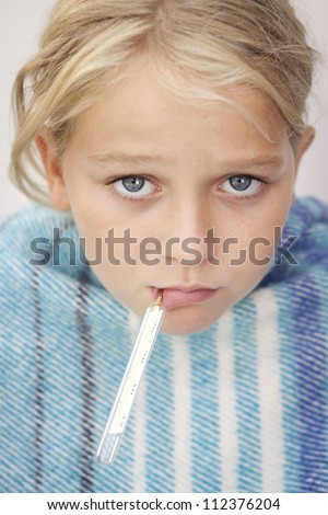 Child with a fever thermometer in her mouth, looking sad and sick - stock photo