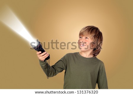 Child with a flashlight looking for something on brown background - stock photo