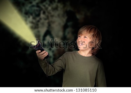 Child with a flashlight looking for something on darkness background - stock photo