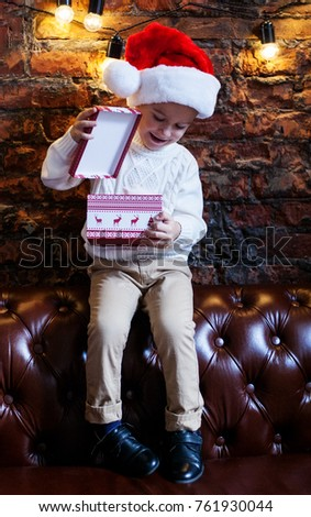 child with a gift, a rabbit in a box, a white sweater, a red hat, a new year