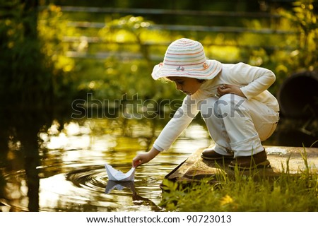 child with a paper boat - stock photo