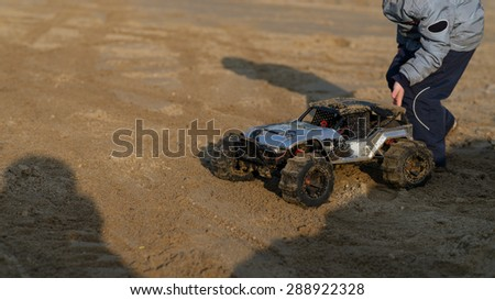 child with a radio-controlled model monster truck on the sandy ground in the park. soft focus and beautiful bokeh - stock photo