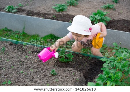 child with a watering can in a garden