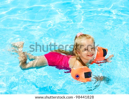 Child with armbands in swimming pool. Summer outdoor. - stock photo