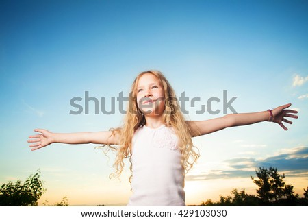 Child with arms outstretched. Freedom. Girl on a background of the sky