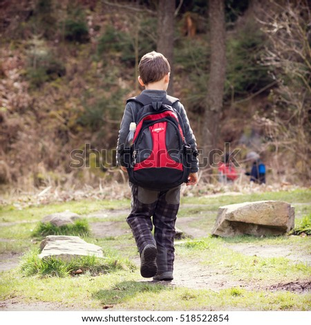 Child with back pack walking or hiking in forest, back view.