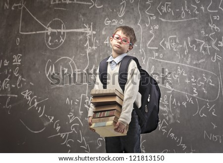 Child with backpack holding some school books with a blackboard in the background - stock photo