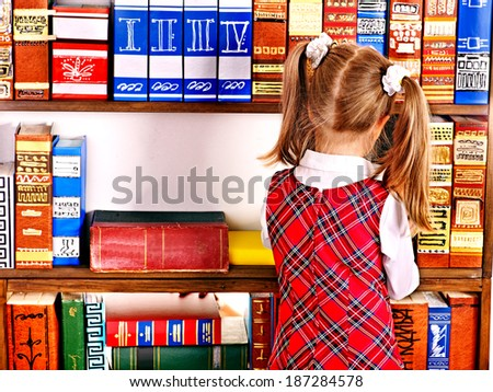 Child with backpack looking on book in library. Rear view. - stock photo