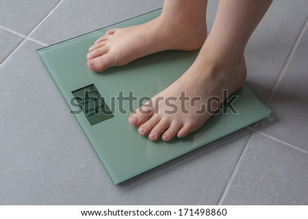 Child with bare feet on a bathroom scale of glass - stock photo