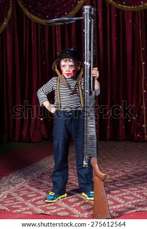 Child with black helmet posing with an upright huge rifle while standing on a carpet with floral decorative pattern - stock photo