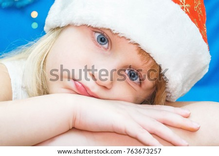 child with blue eyes in santa hat, close up portrait on blue background. Girl is looking thoughtfully