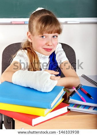 Child with broken arm in classroom. - stock photo