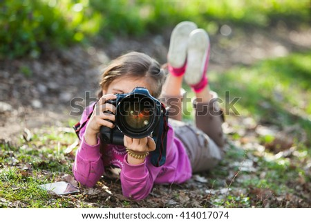 Child with camera. Little girl photographing. beautiful little girl with photo camera. child photographer holding a camera at the park. Young photographer.in nature. - stock photo