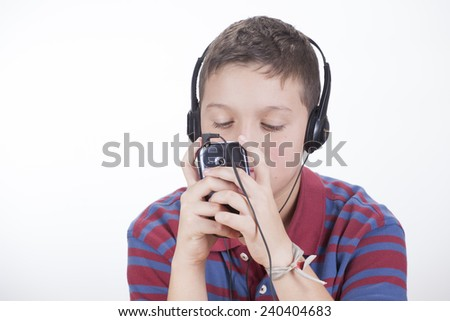 Child with cell phone and headphones on white background