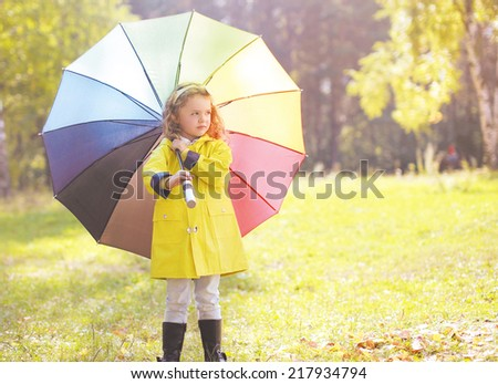 Child with colorful umbrella walking autumn - stock photo