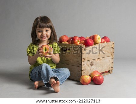 Child with crate of apples.