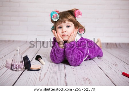 child with curlers in bathrobe - stock photo
