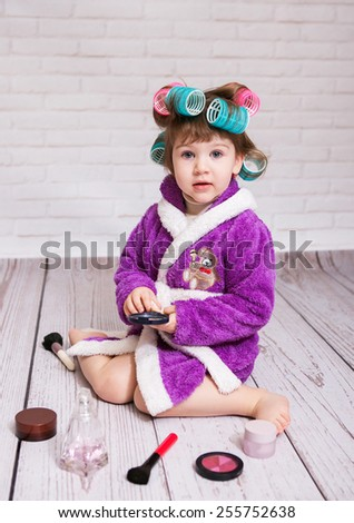 child with curlers in bathrobe