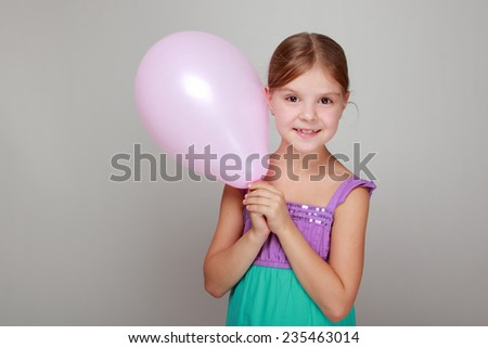 child with cute smile in a bright sundress holding colorful balloons on a gray background - stock photo