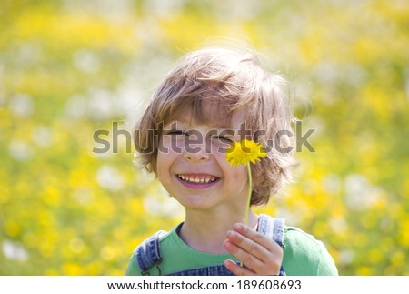 Child with dandelion on a yellow meadow