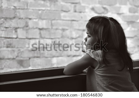 Child with disorder problem (age 3 - 6 ) looks out of a window with brick wall in the background (copy space). concept photo of children health and medical care - stock photo