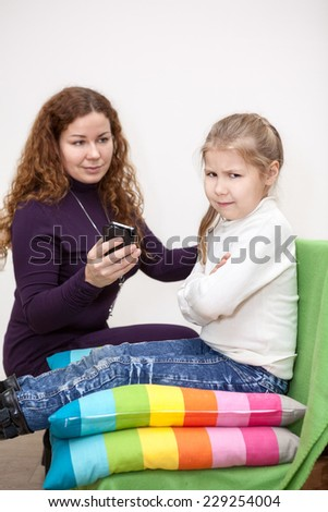 Child with displeasure giving smartphone mother - stock photo