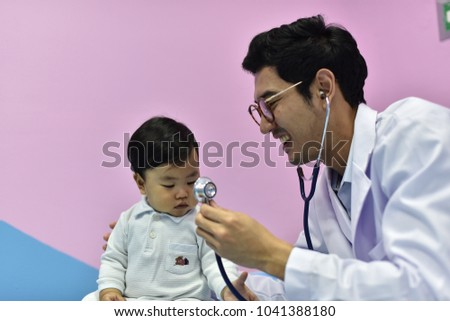 child with doctor.Asian pediatrician is taking care of baby in hospital pediatrician man examining heartbeat of kid boy with stethoscope.