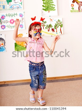 Child with  face painting in play room. Preschooler. - stock photo