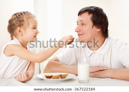 Child with father have a breakfast. Family eating at home - stock photo