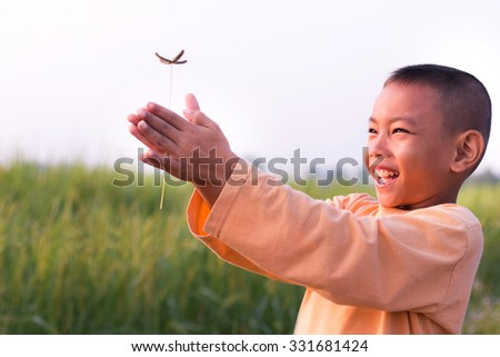 Child with flower on rice field - stock photo
