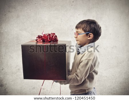 Child with glasses holding a present - stock photo