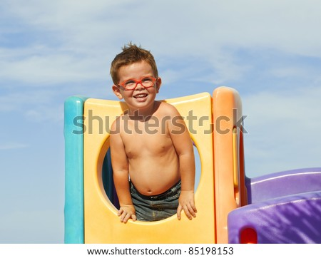 Child with glasses on a summer playground