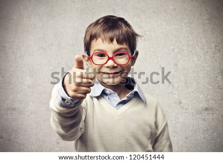 Child with glasses thumbs up - stock photo