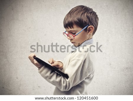 Child with glasses using a laptop computer - stock photo