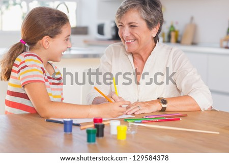 Child with her granny drawing and laughing in kitchen - stock photo