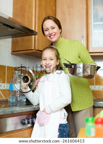 child with her mother prepare the soup by the stove in his kitchen. Focus on the child
