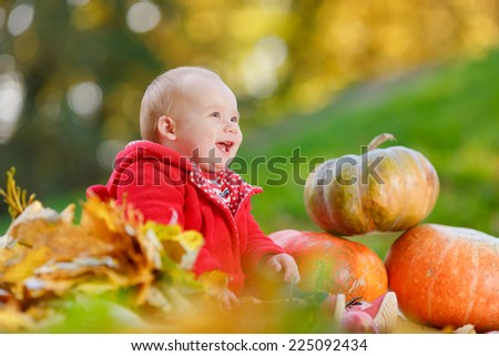 Child with his eyes closed. Happy little child, baby girl laughing and playing in the autumn on the nature walk outdoors.  Cute baby girl with pumpkins in autumn garden. - stock photo