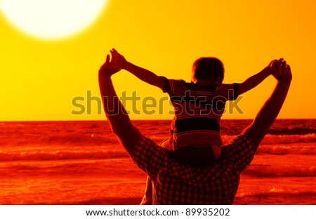 child with his father at sea on sunset