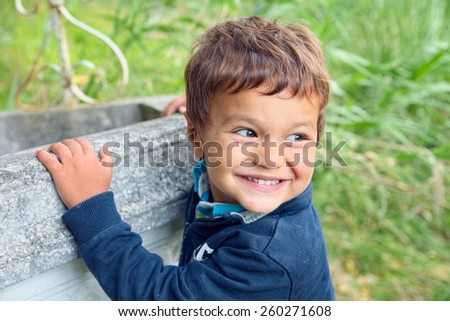 Child with his hands clinging to a well turns to watch his friends smiling