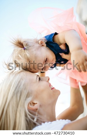 Child with little ponytails leans to mother's hair while she raises her up