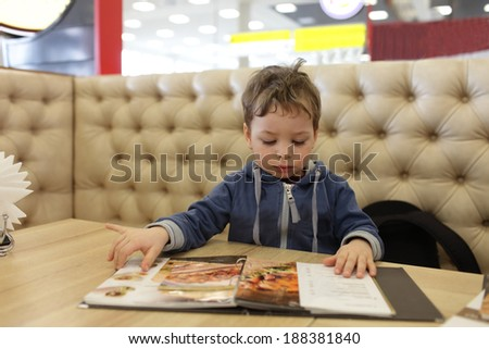 Child with menu at the table in a cafe - stock photo